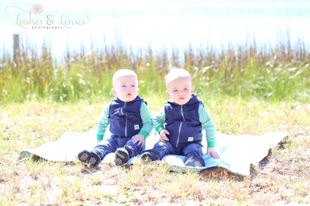 Twin boys sitting by the water