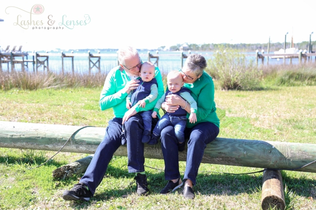 Grandparents with twin boys sitting on log