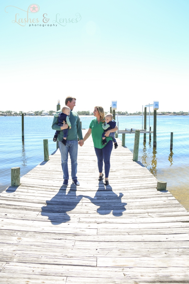 Parents holding baby boys on dock