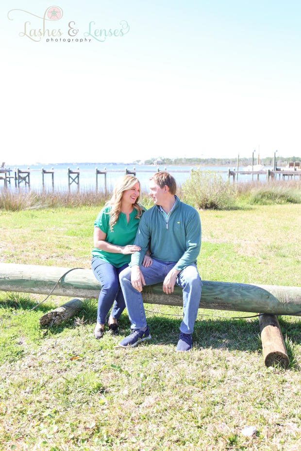Couple sitting on log by the water