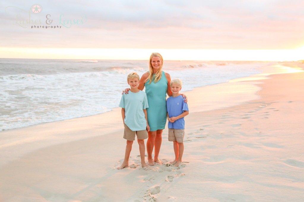 Mom with sons photographed by water at Sunset