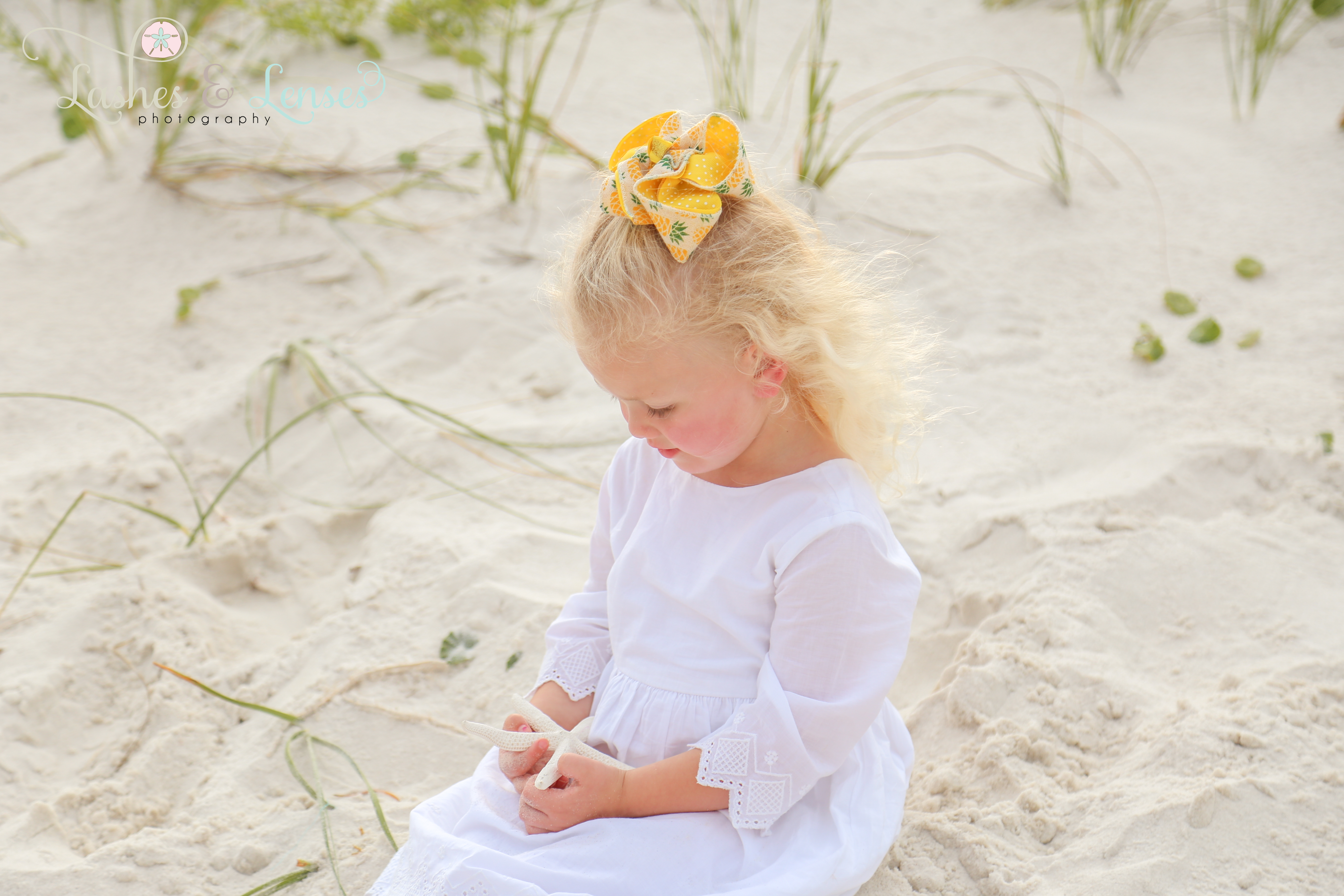 Little girl with starfish in sand