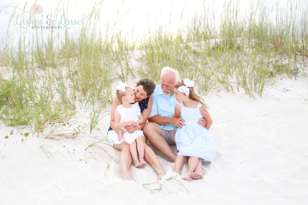 Grandparents sitting in the sand with grandchildren