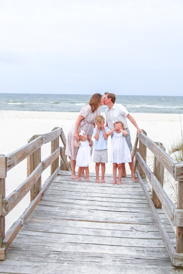 Couple kissing with children photographed on boardwalk at Johnsons Beach Perdido Key