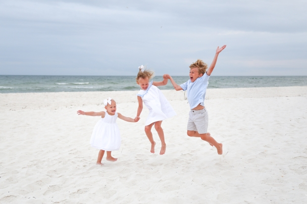 Children jumping in sand at Johnsons Beach Perdido Key