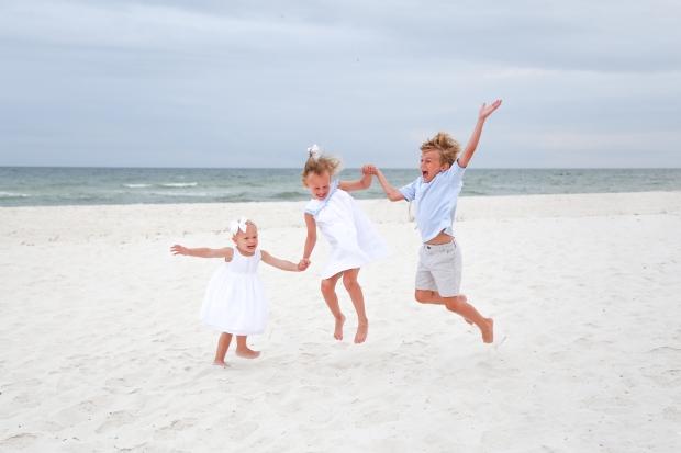 Children jumping in sand at Johnsons Beach Perdido Key