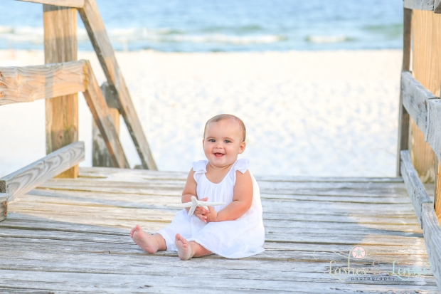 Baby girl sitting on boardwalk at Johnsons Beach Perdido Key
