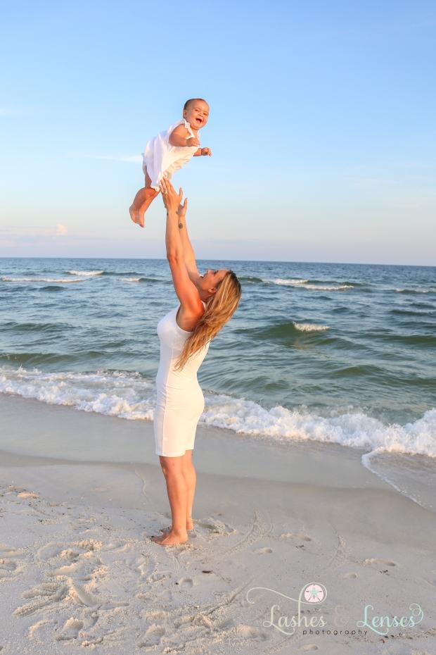 Mom throwing baby in air at Johnsons Beach Perdido Key