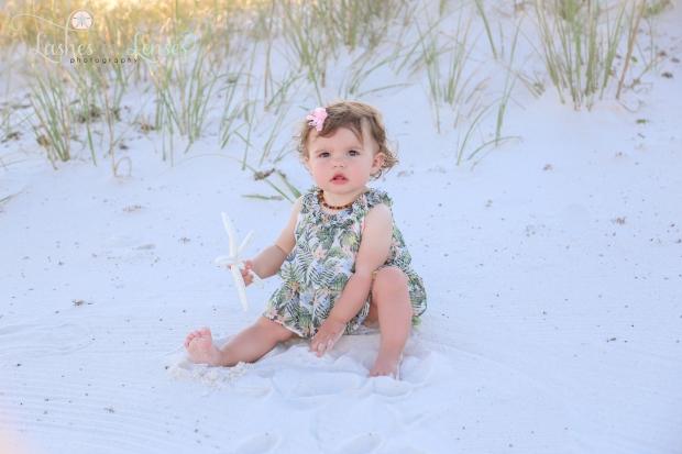 Baby girl sitting in sand at Johnsons Beach Perdido Key