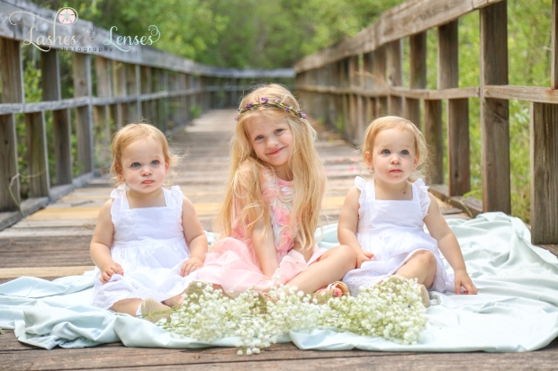 Twin girls and sister sitting on blanket with flowers