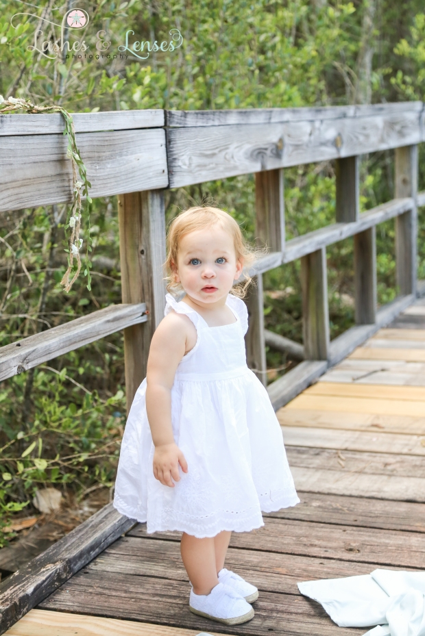 Baby girl standing on boardwalk