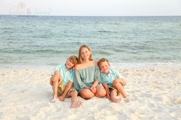 Siblings sitting in sand by the water at Johnsons Beach Perdido Key