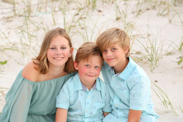 Sister and two brothers sitting in sand at Johnsons Beach Perdido Key