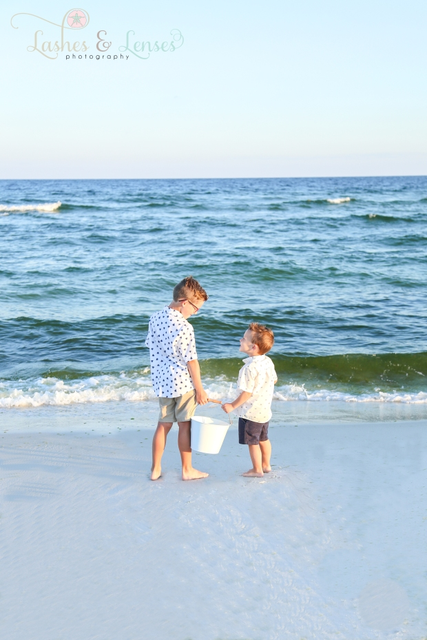 Brothers holding a bucket next to the water at Johnsons Beach Perdido Key