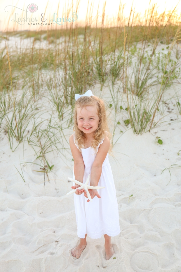 Little girl with starfish in the sand at Johnsons Beach in Perdido Key