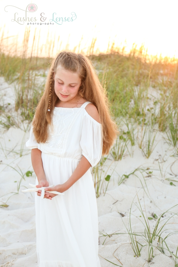 Young teenage girl with starfish at Johnsons Beach in Perdido Key