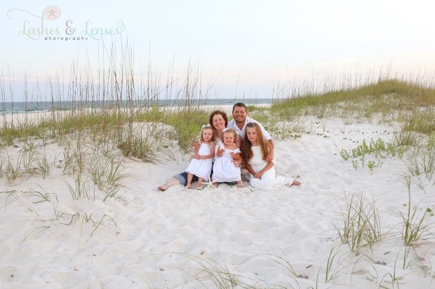Parents with daughters sitting in the sand at Johnsons Beach in Perdido Key