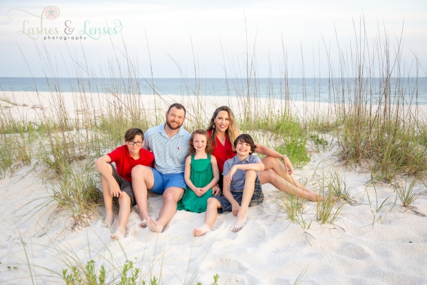 Family sitting in the sand at Johnsons Beach Perdido Key