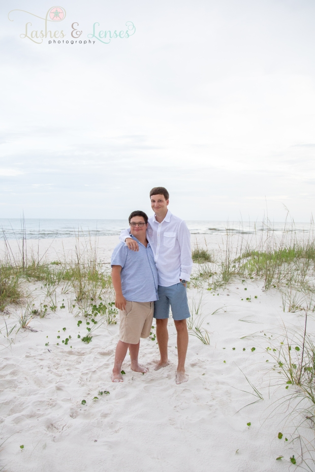 Brothers hugging next to sand dune at Johnsons Beach Perdido Key