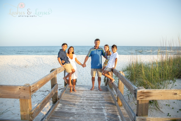 Family with three children standing on the boardwalk at Johnsons Beach Perdido Key