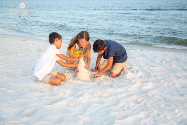 Siblings building a sandcastle next to the water at Johnsons Beach Perdido Key