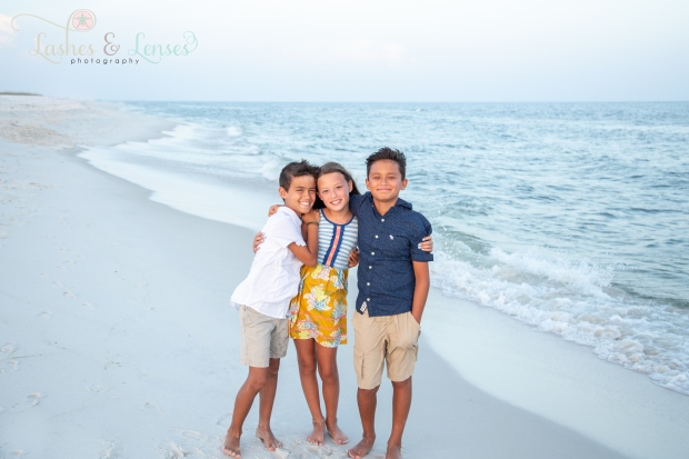 Brothers and Sister hugging next to the water at Johnsons Beach Perdido Key