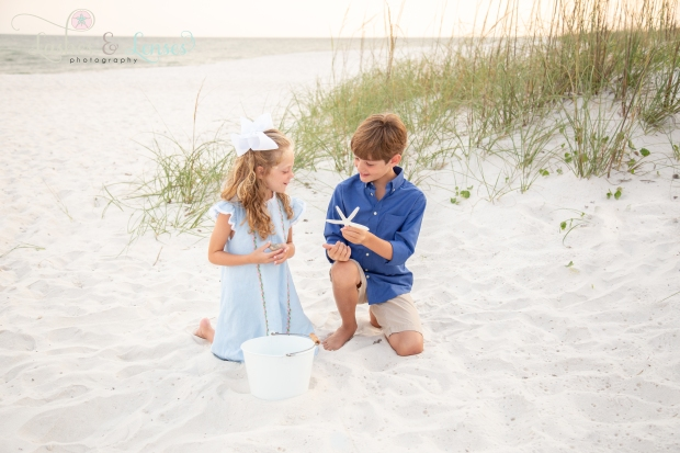 Brother and Sister sitting in the sand looking at a starfish at Johnsons Beach Perdido Key