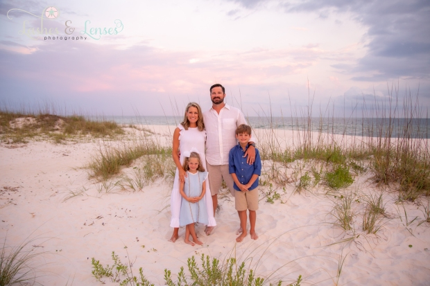Family standing next to a sand dune at Johnsons Beach Perdido Key