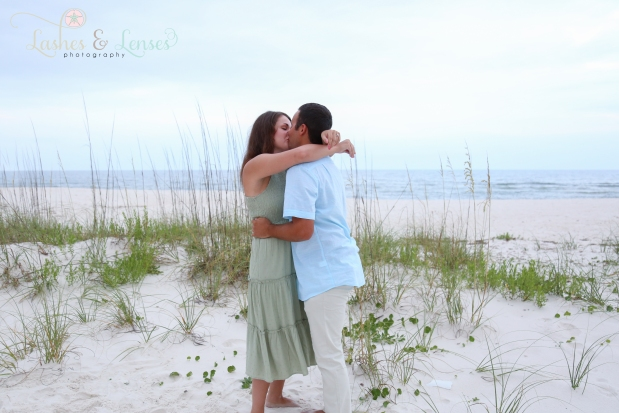 Engaged couple kissing in the sand at Johnsons Beach Perdido Key