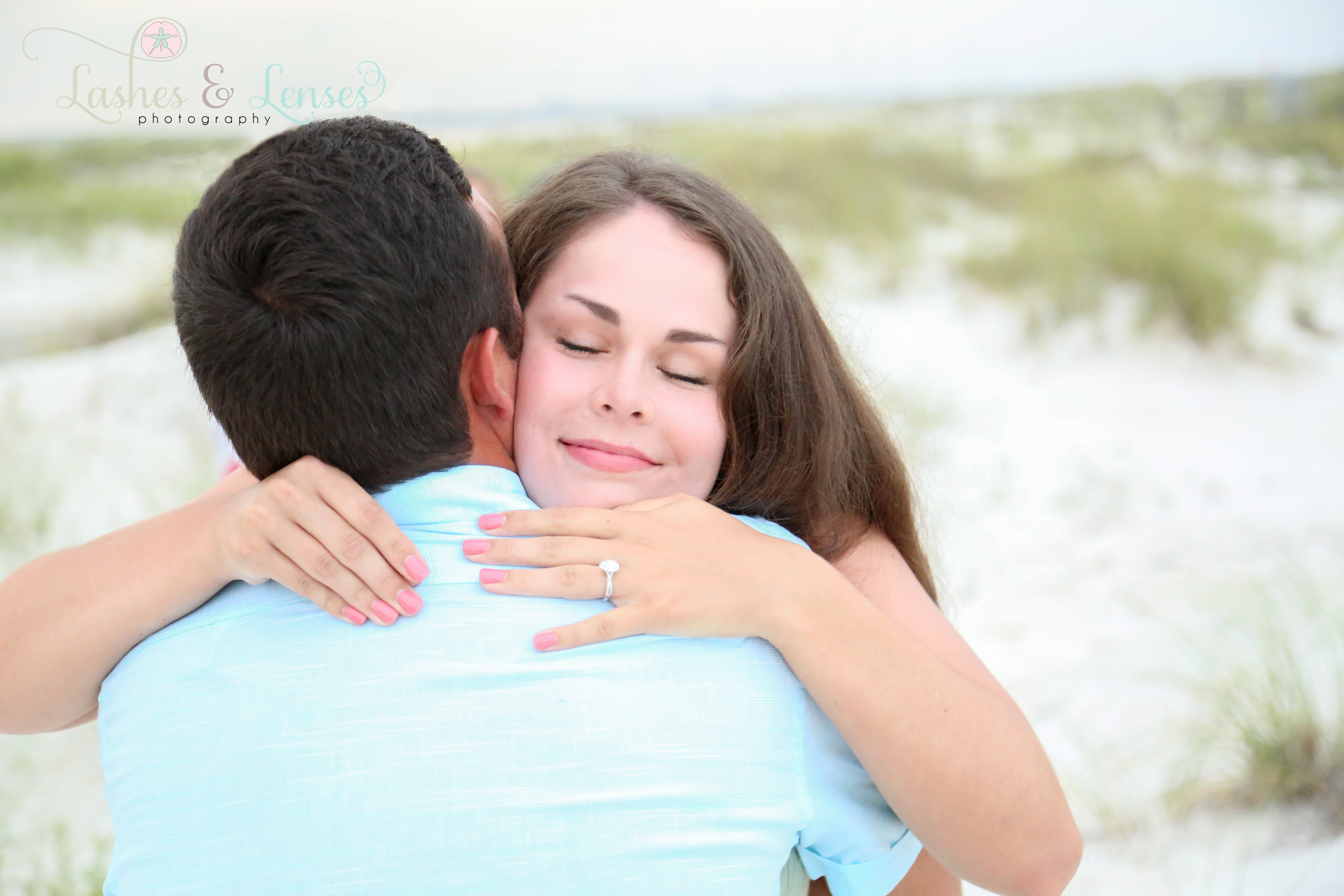 Couple hugging and showing off ring at Johnsons Beach Perdido Key