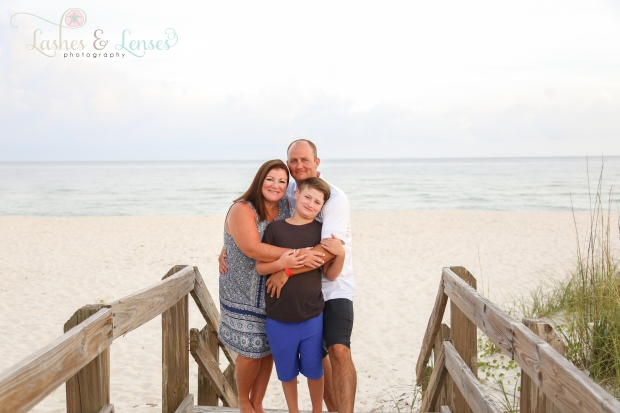 Family with preteen son on boardwalk at Johnsons Beach Perdido Key