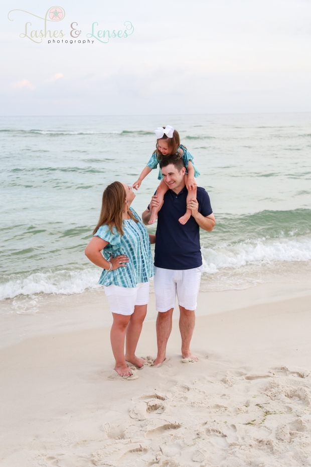 Parents with daughter on Dads shoulders next to the water at Johnsons Beach Perdido Key