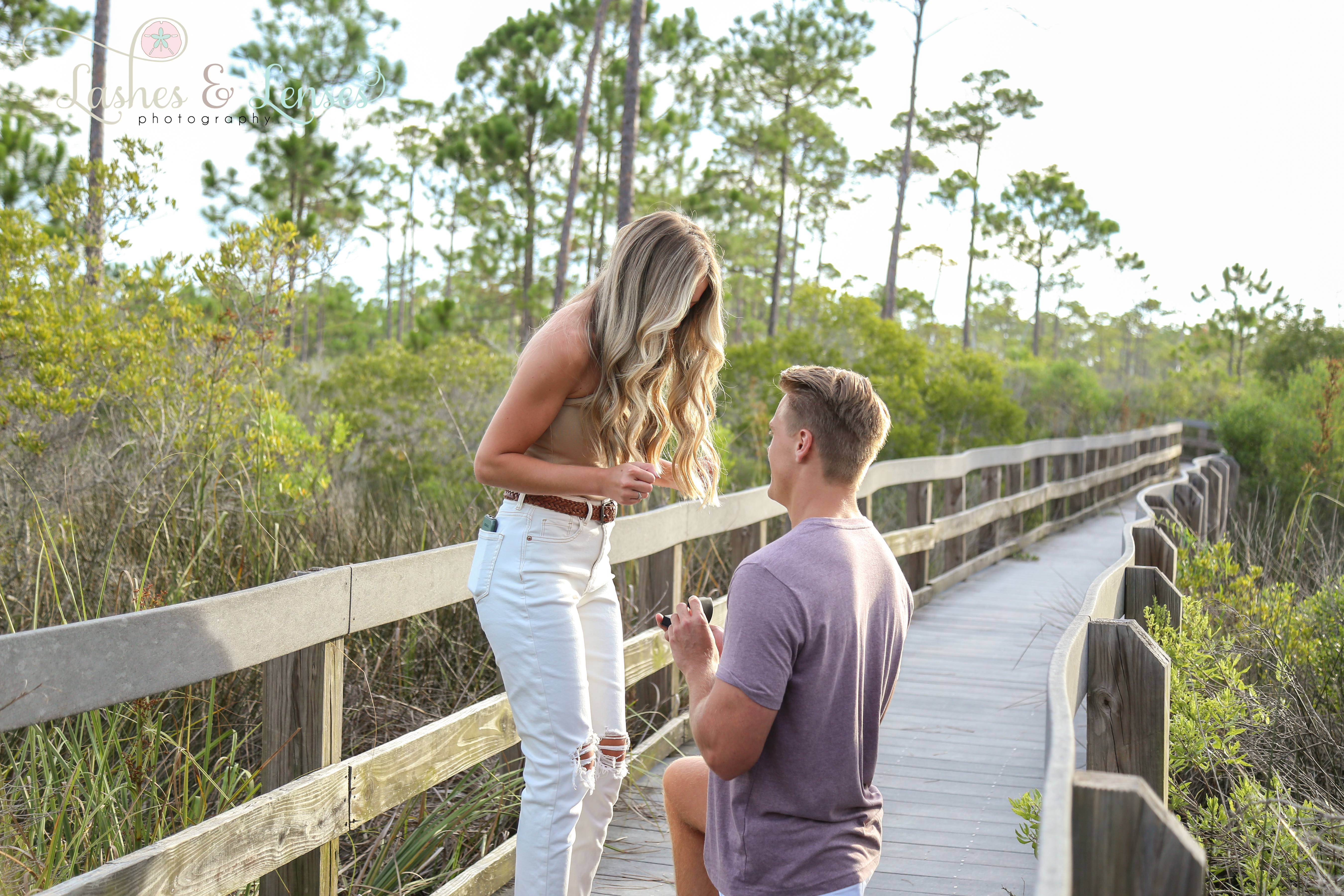Young man proposing down on one knee to girlfriend on nature trail at Johnsons Beach Perdido Key