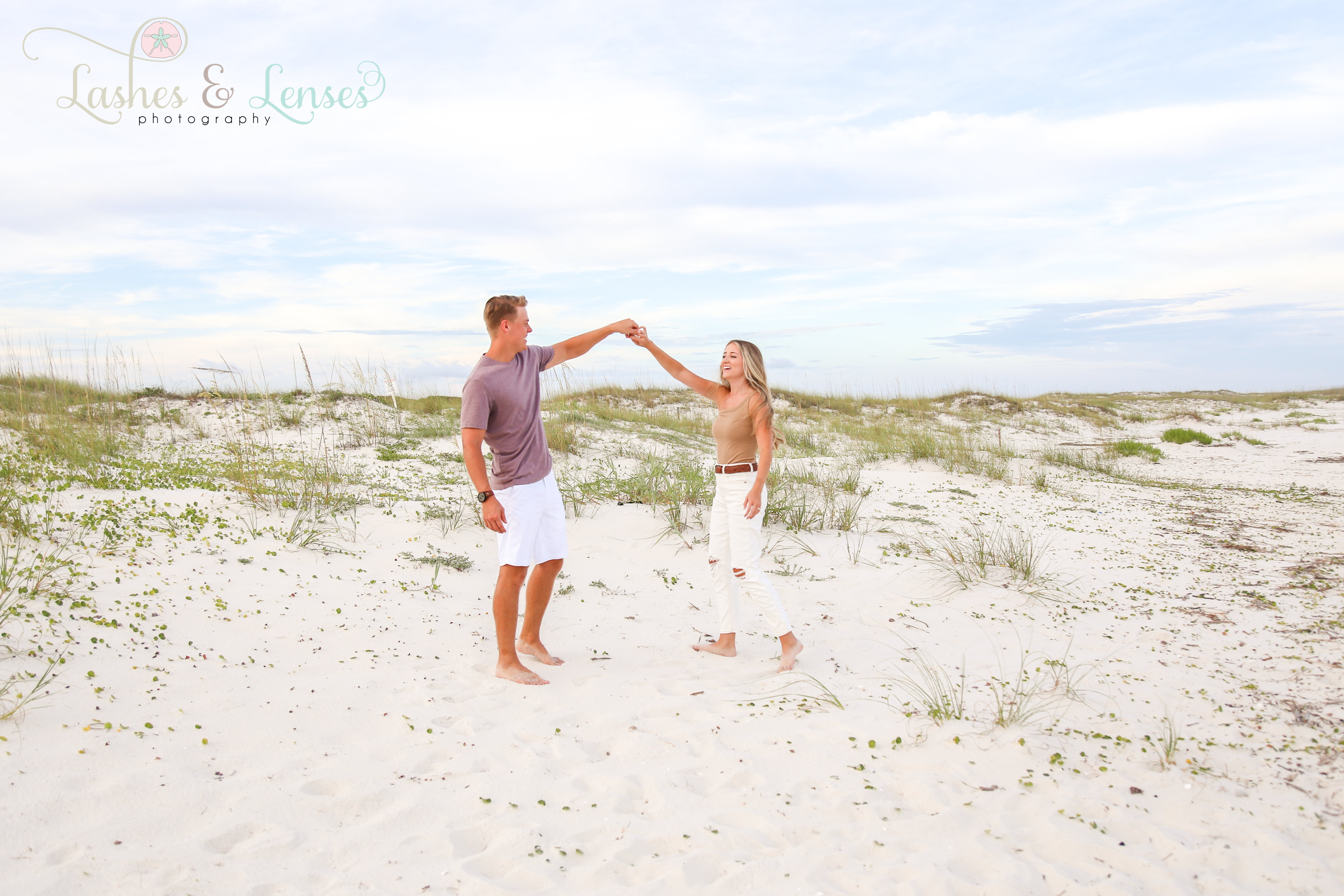 Engaged couple dancing in the sand at Johnsons Beach Perdido Key