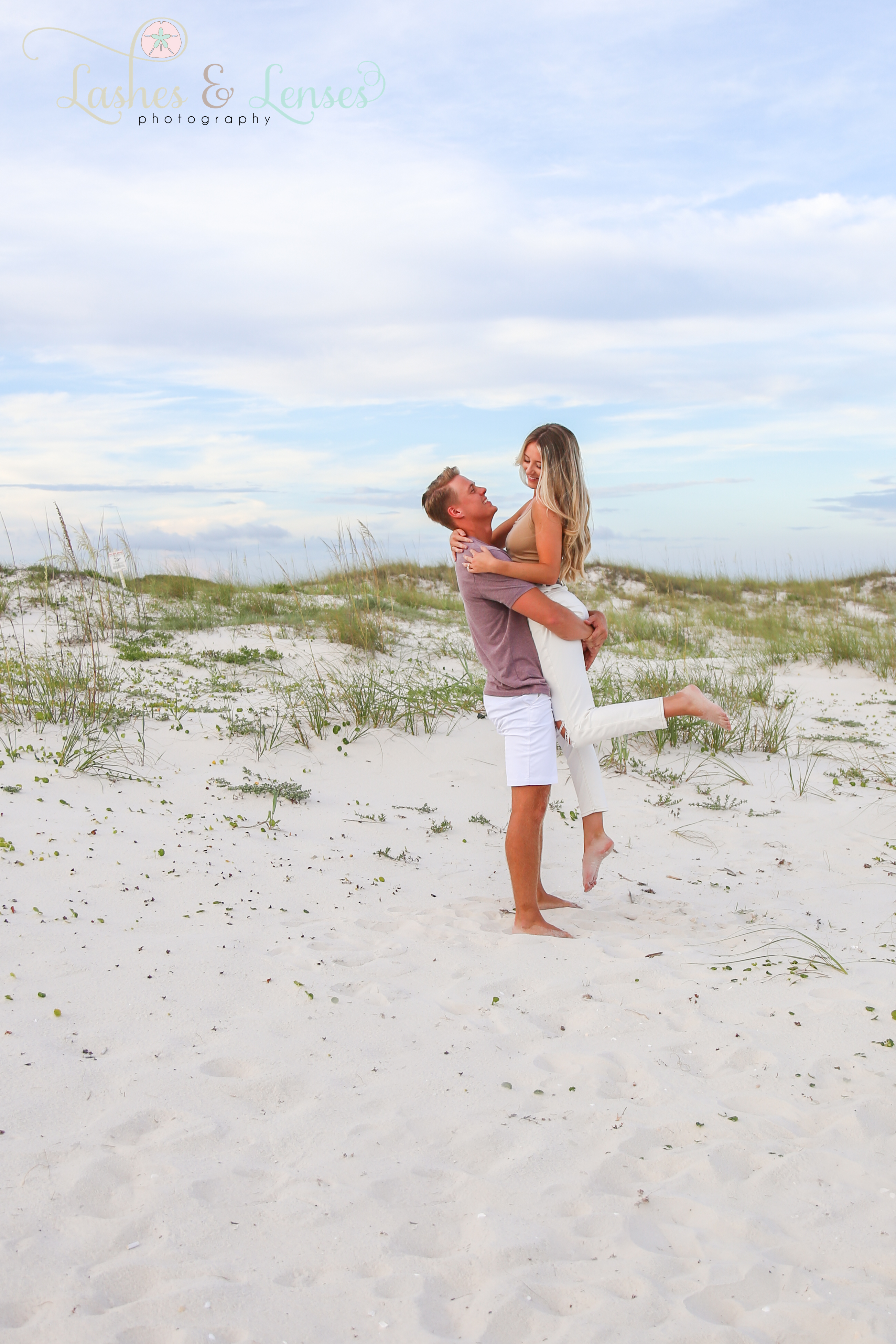 Young man holding girlfriend up in the air at Johnsons Beach Perdido Key