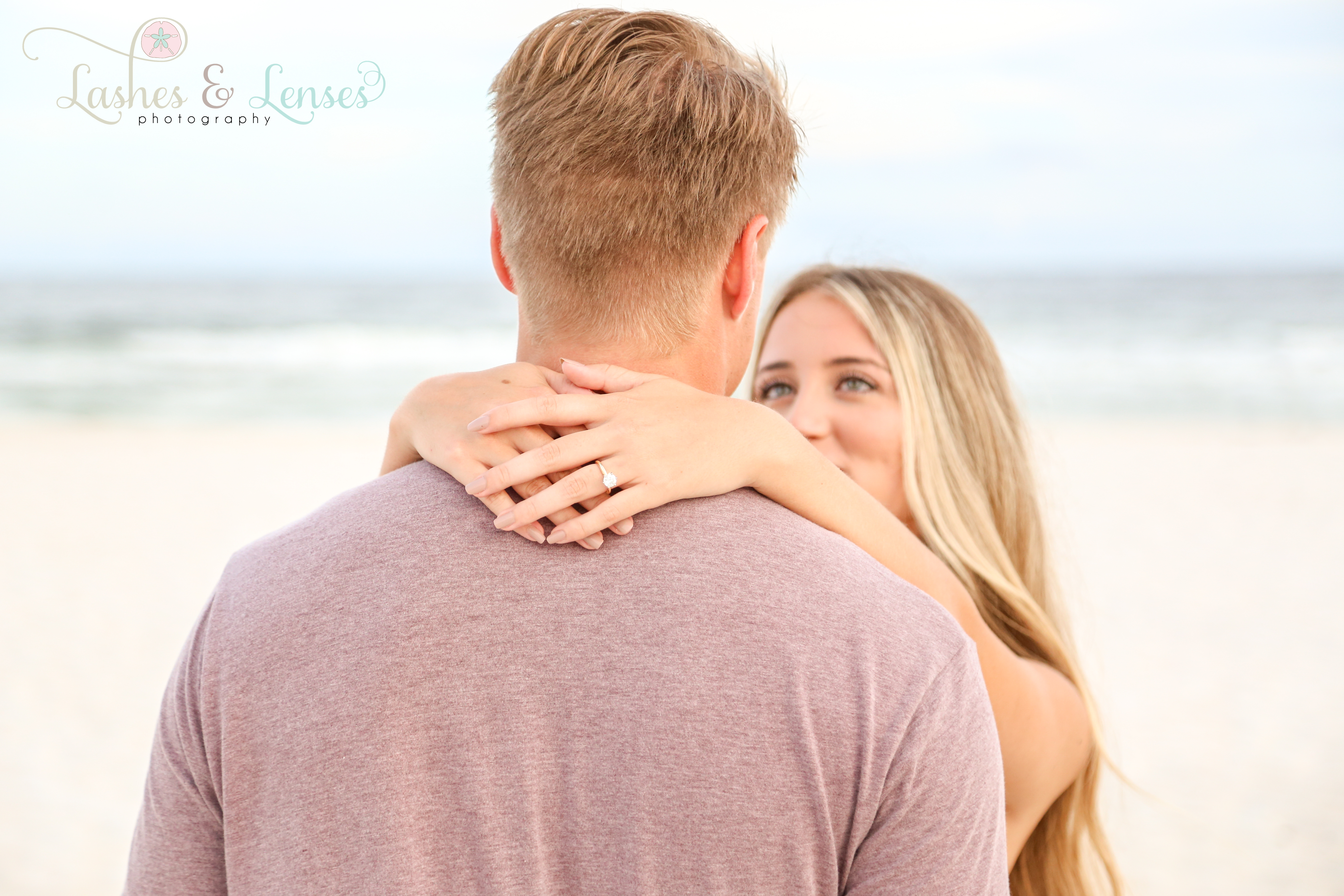 Young woman with hands around her fiancés neck at Johnsons Beach Perdido Key
