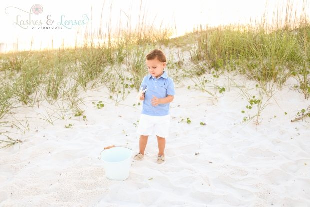 Toddler boy holding a starfish next to a sand dune at Johnsons Beach in Perdido Key