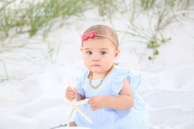 Baby girl sitting in the sand holding a starfish at Johnsons Beach in Perdido Key