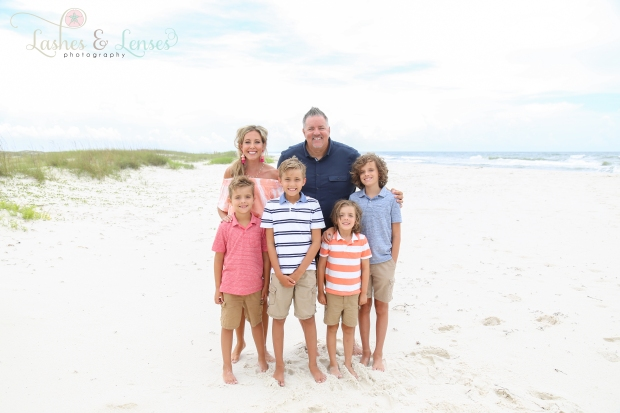 Mom and dad with their four sons standing in the sand at Johnsons Beach in Perdido Key