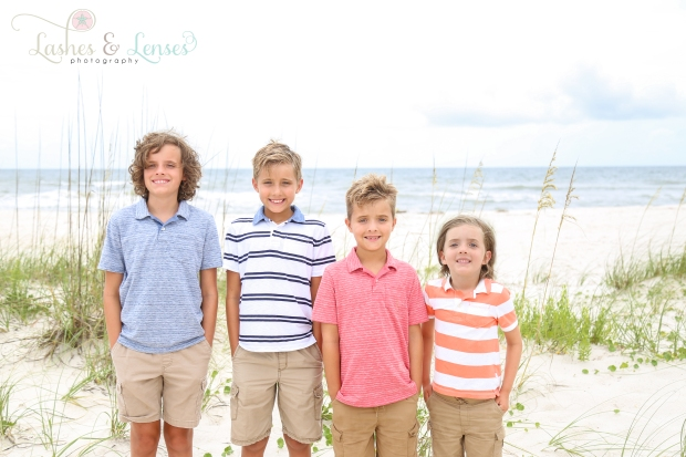 Four brothers standing next to a sand dune at Johnsons Beach in Perdido Key