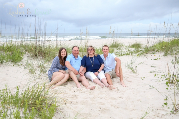 Mom and Dad sitting in the sand with their grown children at Johnsons Beach in Perdido Key