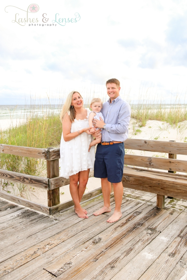 Mom and Dad with baby boy on the boardwalk at Johnsons Beach in Perdido Key