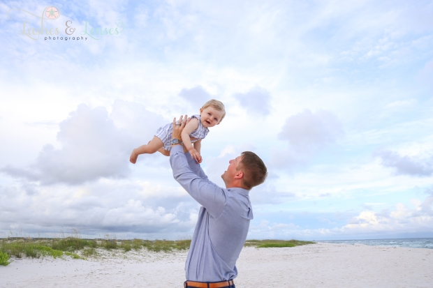 Dad holding son up in the air on the beach at Johnsons Beach in Perdido Key