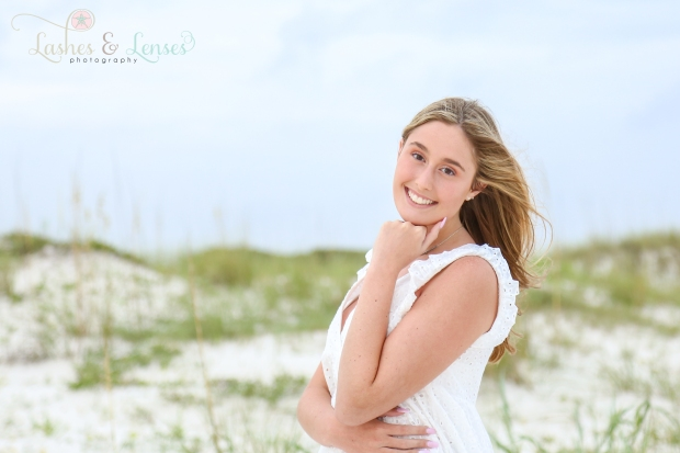 Blonde senior girl posing on the beach next to a sand dune at Johnsons Beach in Perdido Key