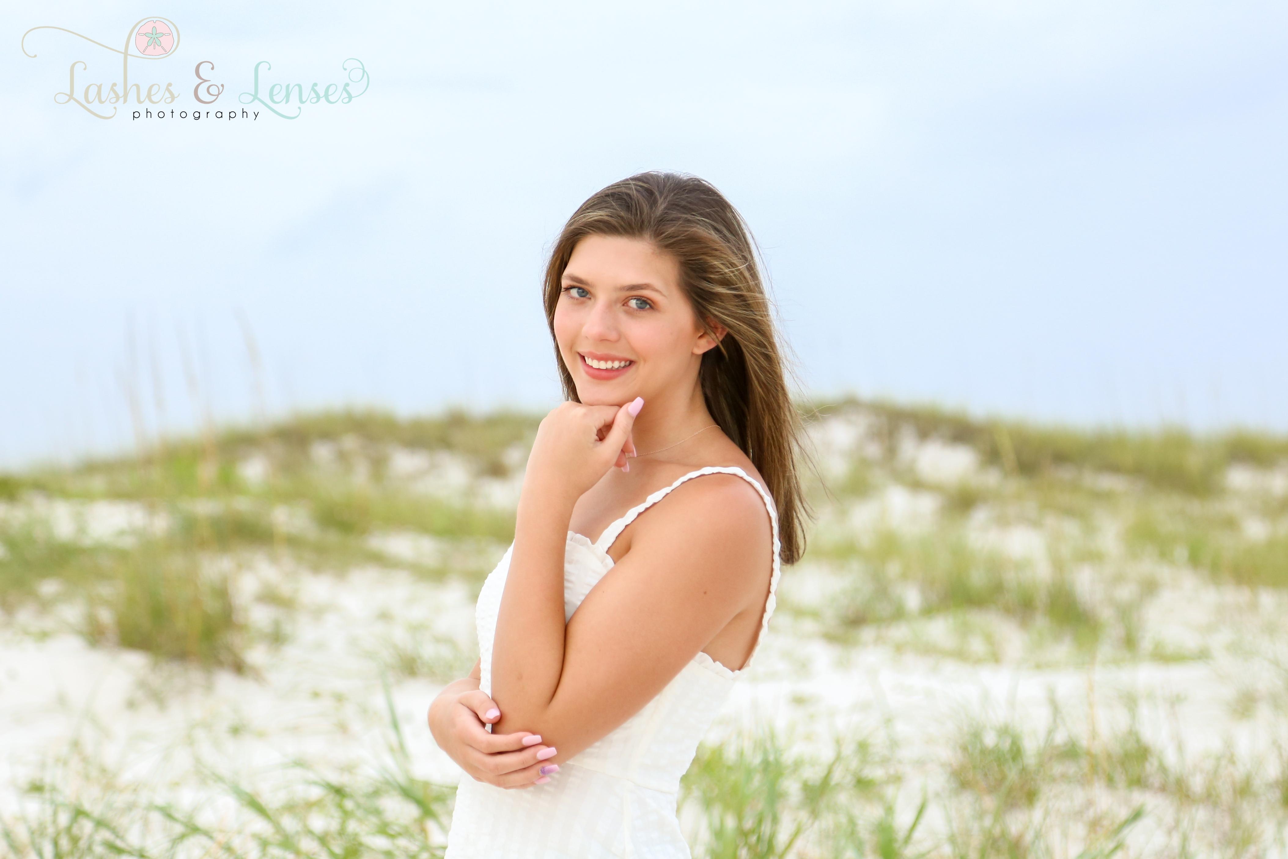 Brunette senior girl posing on the beach next to a sand dune at Johnsons Beach in Perdido Key