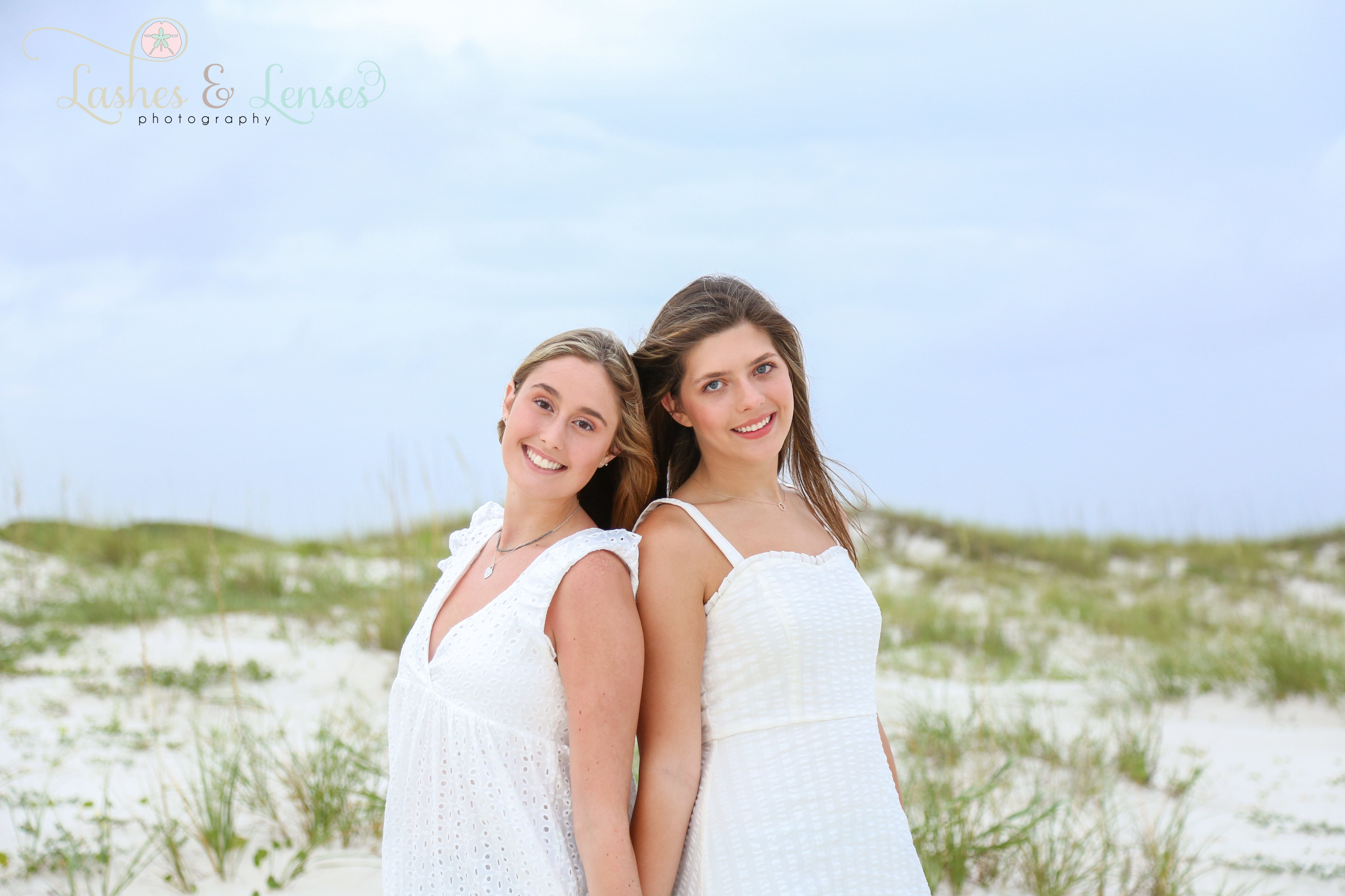 Two senior girls posing on the beach next to a sand dune at Johnsons Beach in Perdido Key