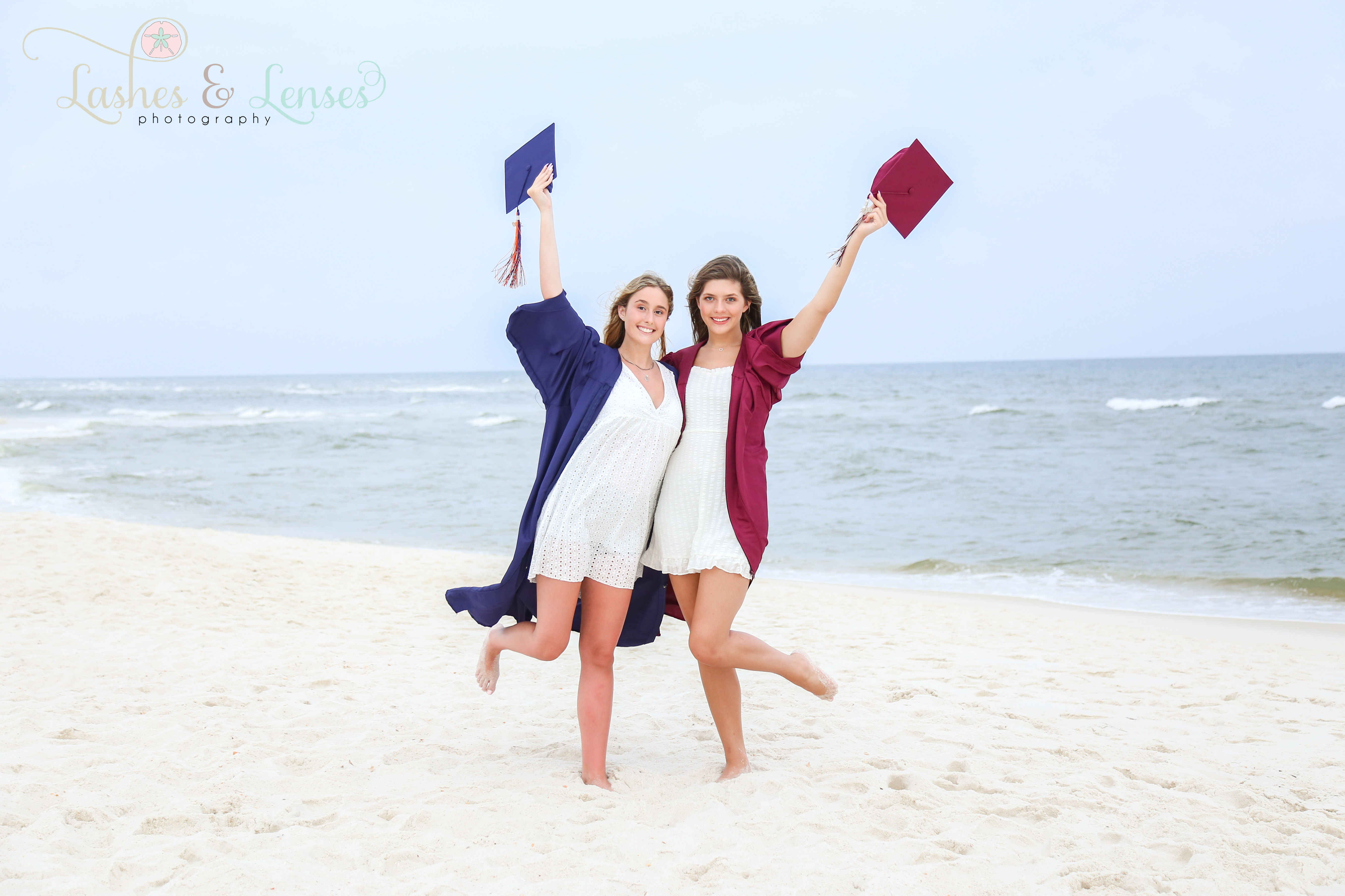 Two senior girls in their caps and gowns on the beach at Johnsons Beach in Perdido Key