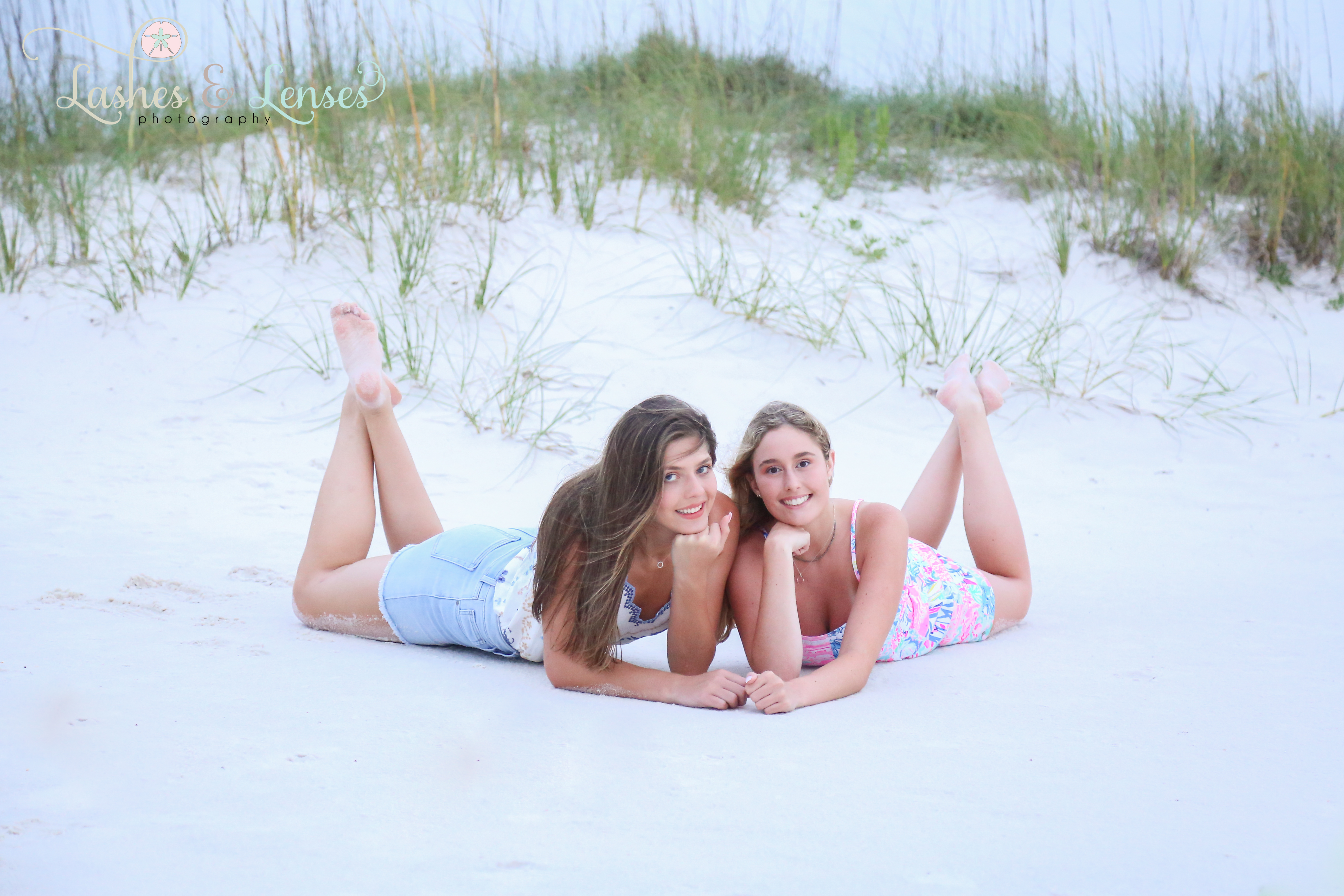 Two senior girls laying on the sand at Johnsons Beach in Perdido Key