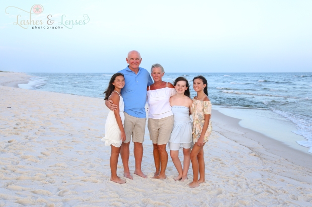 Grandma and Grandpa with their three granddaughters by the waters edge at Johnson Beach Perdido Key