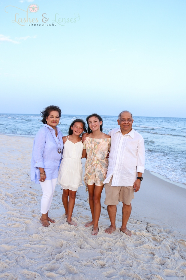 Grandparents with their two granddaughters by the water at Johnson Beach Perdido Key
